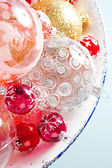 Bunch of different size and design christmas balls in a silvery dish — Stock Photo