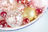 Various Christmas balls on a glitter container — Stock Photo