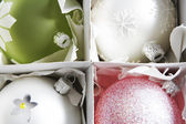 Four decorted Christmas balls sitting in a box with partitions. — Stock Photo