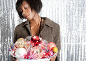 Young black woman holding a dish full of christmas barballs — Stock Photo