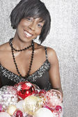 Attractive black woman holding Christmas barballs — Stock Photo