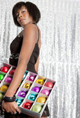 Young balck woman holding a box with different color christmass balls — Stock Photo