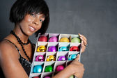 Attractive black woman holding a box full of various christmas barballs — Stock Photo