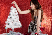 Attractive young woman decorating a small christmas tree — Stock Photo