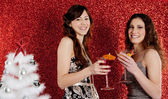 Two young women drinking cocktails and having fun with a christmas tree — Stock Photo