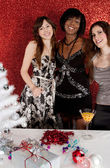 Three women friends smiling at a christmas party — Stockfoto