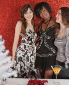 Three women friends smiling at a christmas party — Stok fotoğraf