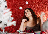 Attractive young woman decorating a white Christmas tree — Foto Stock