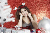 Young woman sitting at Christmas table surrounded by ornaments and gifts — Stock Photo