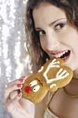 Young attractive woman biting a Christmas decorated buiscuit. — Stock Photo