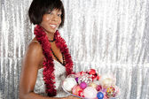 Young black woman holding a dish full of Christmas barballs tree decorations — Stock Photo