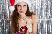 Attractive young woman holding christmas tree barballs in her hands — Stock Photo
