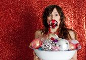 Jovem mulher, segurando um prato cheio de bolas de natal bar com um na boca dela — Foto Stock