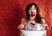 Young woman holding a dish full of Christmas bar balls with one of them in her mouth — Стоковое фото