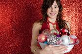 молодая женщина, держащая блюдо полный бар игрушки на елку — Стоковое фото