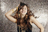 Young attractive woman dancing against a silver glitter background — Stock Photo