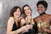 Three women toasting with champagne at a party — Стоковое фото