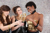 Three young women toasting with champagne at a party — Photo