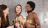 Three women toasting with champagne at a party against — Stockfoto