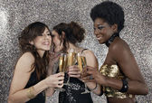 Three girls toasting with champagne at a party — Stock Photo