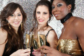 Three young women toasting with champagne at a party — Stok fotoğraf
