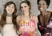 Three girls with a birthday cake and candles against a silver glitter background — Stock Photo