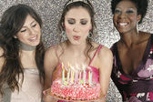Birthday girl blowing birthday cake's candles with friends. — Stock Photo