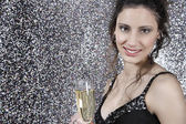 Girl holding a glass of champage against a silver glitter background — Stock Photo