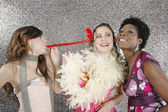 Three girls celebrating with party blowers — Stock Photo