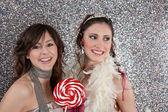 Due giovani donne, una festa e mangiare caramelle contro uno sfondo argento gitter. — Foto Stock