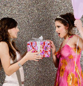 Young woman offering a gift to a birthday girl at a party — Stock Photo