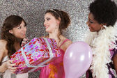 Three young women at a birthday party offering presents — Stok fotoğraf