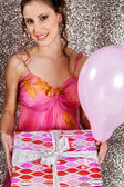 Young woman holding a wrapped gift and a pink balloon — Stock Photo