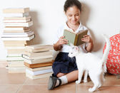 Young girl reading a book with her cat at home — Stock Photo