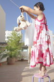 Young girl hanging her dog soft toy to dry on the washing line at home — Stock Photo