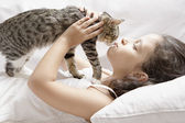 Young girl kissing kitten while laying down on a white sofa at home. — Stock Photo