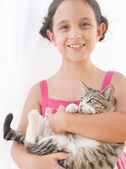 Close up portrait of a young girl holding a kitten in her arms — Stockfoto