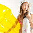 Young woman holding a yello lilo being ready for a beach holiday — Stock Photo