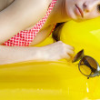 Teenage girl laying down on an inflatable yellow lilo — Stock Photo #22110655