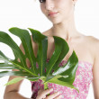 Attractive young woman holding a large green leaf  — Stok fotoğraf