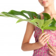 Beauty detail view of a young woman holding tropical green leaf — Stock Photo
