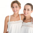 Two young women wearing white tops and standing with arms around each other — Stock Photo