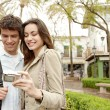 Young couple taking a picture of themselves while on vacation in a picturesque town square — Stock Photo #22111235