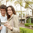 Young couple taking a picture of themselves while on vacation in a picturesque town square — Stock Photo