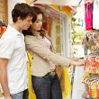 Young attractive couple shopping in a market stall while on vacation. — Stock Photo