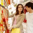 Young attractive couple shopping for clothes in a market stall while on vacation. — Stock Photo