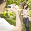 Young man taking a picture of his girlfriend while on vacations in a town square. - Stockfoto