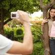 Young couple taking pictures of each other while in a park on holidays. — Stok fotoğraf