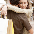 Young couple hugging and smiling with shopping bags — Stock Photo #22111413