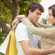 Portrait of a young couple hugging and smiling with shopping bags — Stock Photo